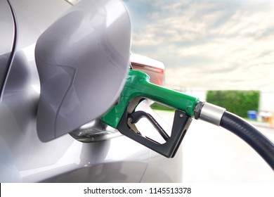 Closeup of filling benzine gasoline fuel in car at gas station.Refuel with nozzle machine at petrol gas pump service.