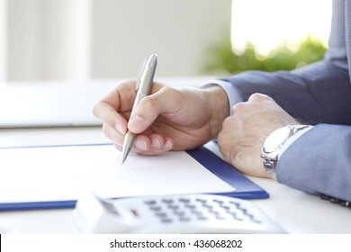 Close-up of financial director working on business plan while sitting at office in front of computer.