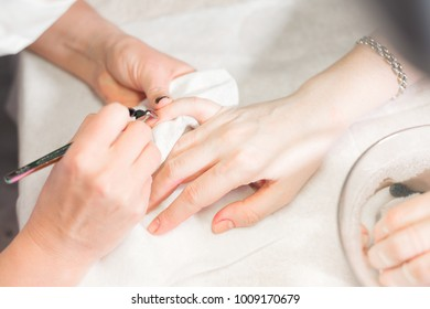 Closeup finger nail care by manicure specialist in beauty salon. Manicurist clear cuticle professional nippers for manicure and pedicure.