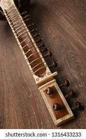Close-up of a fingerboard Indian musical instrument sitar lying on a wooden floor - image