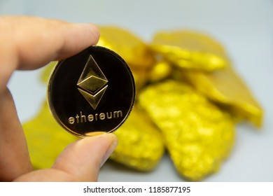 closeup fingers hold the ethereum coin in front of gold chunks