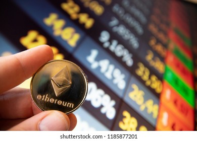 closeup fingers hold the ethereum coin in front of stock market screen