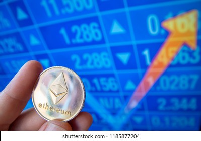 closeup fingers hold the ethereum coin in front of stock market screen which is rising