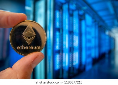 closeup fingers hold the litecoin coin in front of super computer in server room