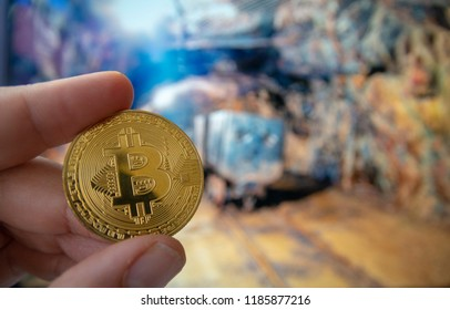 closeup fingers hold the litecoin coin in entrance of real mine