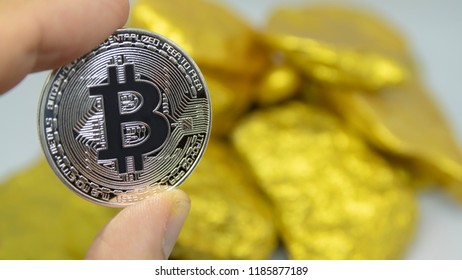 closeup fingers hold the silver bitcoin coin in front of gold chunks