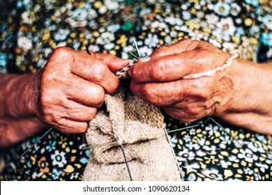 Closeup of fingers of a old woman is making yarn for knitting from natural rough sheep wool (natural fiber) on traditional way
