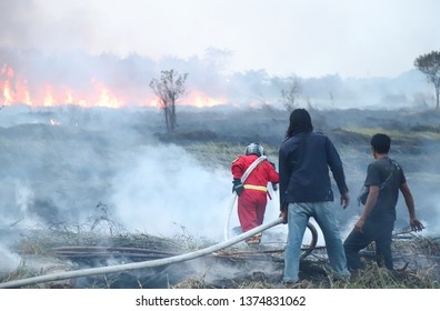 Closeup of firefighter in red uniform and volunteer team doing his work to control extensive fire in agricultural field in very hot summer evening. Thailand.