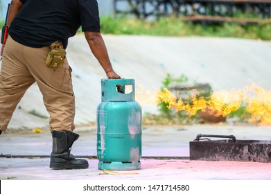 Closeup of firefighters lower body training for fire drill by demonstrate how to close the gas tank valve correctly. Security insurance protection and fire fighter concept. Occupation and volunteer