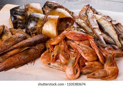 closeup fish background. smoked seafood fish and shrimp. herring, perch, capelin, mackerel home smoking.