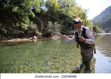 Closeup of fisherman fly fishing in freshwater river