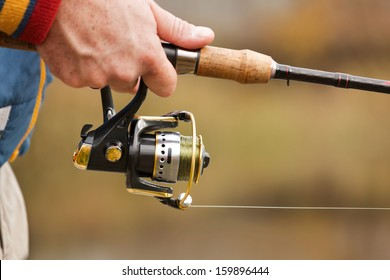 Closeup of Fisherman`s hand with spinning - autumn fishing season.
