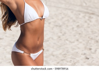 Close-up of fit bikini stomach abs. Woman with beautiful body on a tropical beach