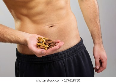 Closeup of fit healthy young Caucasian man's hands holding organic nuts. Nutrition, healthy lifestyle and diet concept.