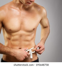 Closeup of fit muscular shirtless Caucasian man with caliper measuring his fat level. Square image, dark gray background, diet, fitness and healthy lifestyle concept.
