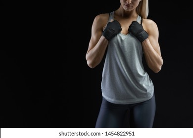 Close-up of fit woman's torso with her hands on chest. Female with perfect muscles on black background with copyspace. Women health energy fitness motivation.