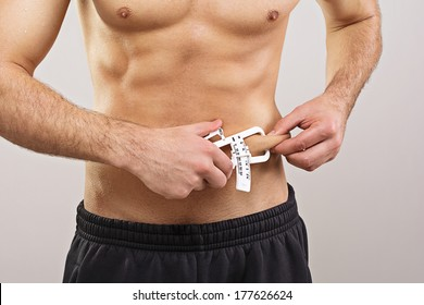 Closeup of fit young man measuring body fat percentage using caliper. Diet, fitness, keto and healthy lifestyle and body care concept.