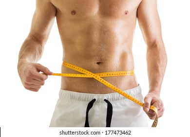 1fd135d393d Closeup of fit young man s body. Man measuring his waist with tape measure.  Isolated