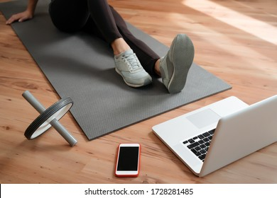 Closeup fit young woman with perfect body doing exercises at home while watching video workout classes on laptop. Practicing yoga online. Home fitness during coronavirus quarantine and self isolation