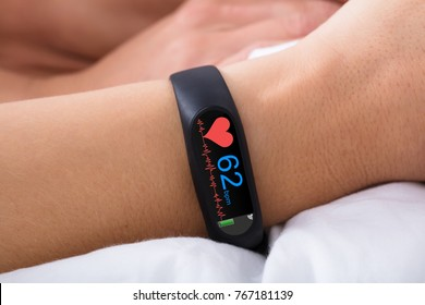 Close-up Of Fitness Activity Tracker With Heartbeat Rate On Woman's Hand Over Bed
