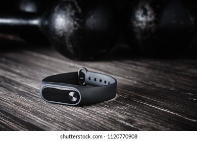 Closeup fitness tracker and old dumbbells on dark wooden background