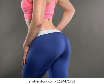 Closeup of fitness woman with fit cheeks, tight hips and firm buttocks in workout leggins. Perfect female ass in shape of sexy bottom and big butt. Slim girl body isolated on white background.
