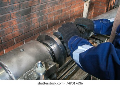 Close-up of a fitter in a blue uniform working on on an automatic welding machine for the repair.  The man works at the plant for repair cardan shafts