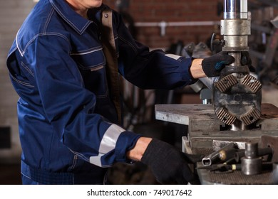 Close-up of a fitter in a blue uniform working on on an automatic welding machine for the repair.  The man works at the plant for the production of cardan shafts