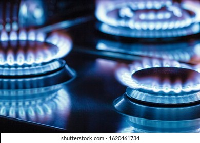Closeup of flame gas nozzles on a stove on a dark background.