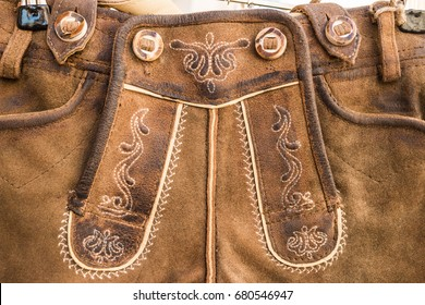 Closeup of flap (drop front) of  traditional bavarian and austrian lederhosen (leather pants). Lether relief and embroidered ornament. Decor elements.