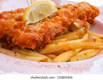 Closeup of flash fried fish and chips on plate with lemon slice