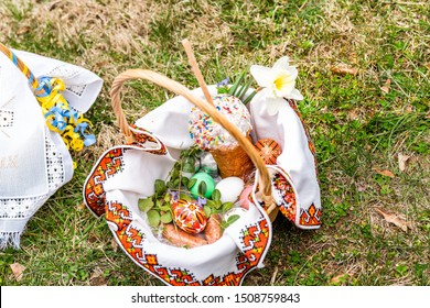 Closeup flat top of Ukrainian Orthodox Easter blessing wicker straw basket with nobody on grass ground outside at church and daffodil spring flowers