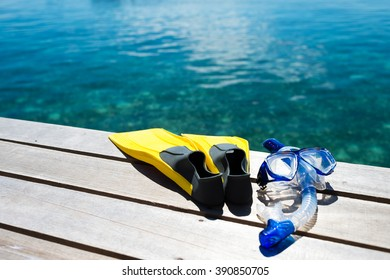 Close-up of flippers and snorkel on pier near sea.