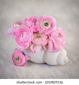 Close-up floral composition with a pink Ranunculus flowers in a shell-shaped vase.