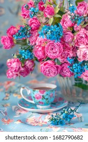 Close-up floral composition with a pink roses and porcelain cups. Many beautiful fresh pink roses on a table.