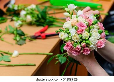 closeup florist making a bouquet of flowers. Shallow depth of field, focus on the bouquet