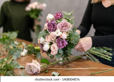 Close-up flowers in hand. Florist workplace. Woman arranging a bouquet with roses, carnation and other flowers. A teacher of floristry in master classes or courses