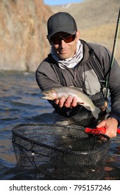 closeup fly fisherman holding a rainbow trout