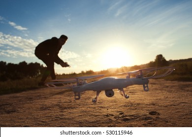 Close-up of flying drone at sunset, free space on sky background. Silhouette of young man, piloting quadrocopter outdoor. Leisure, entertainment, innovation, modern technologies concept