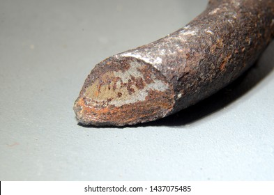 Closeup with focus on the surface of a fracture in a car spring. This spring broke because of metal fatigue. The fracture has a matte crystalline surface, and some flaws and penetrative rust is seen