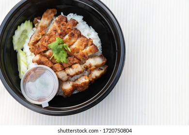 Closeup of food as Crispy fried pork belly with Thai spicy sauce, cucumber on white jasmine rice in black modern bowl on clean cream minimal clolor  table cloth background and texture with copy space.