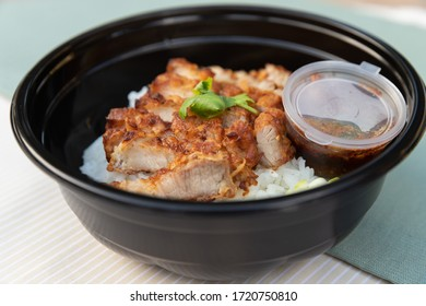 Closeup of food as Crispy fried pork belly with Thai spicy sauce, cucumber on white jasmine rice in black modern bowl on clean cream and green minimal clolor table cloth background and texture.