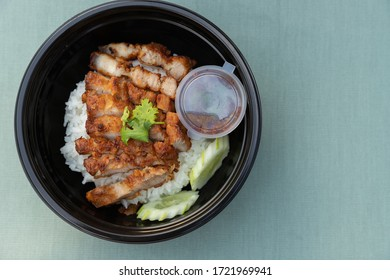 Closeup of food as Crispy fried pork belly with Thai spicy sauce, cucumber on white jasmine rice in black modern bowl on clean green minimal clolor  table cloth background and texture with copy space.
