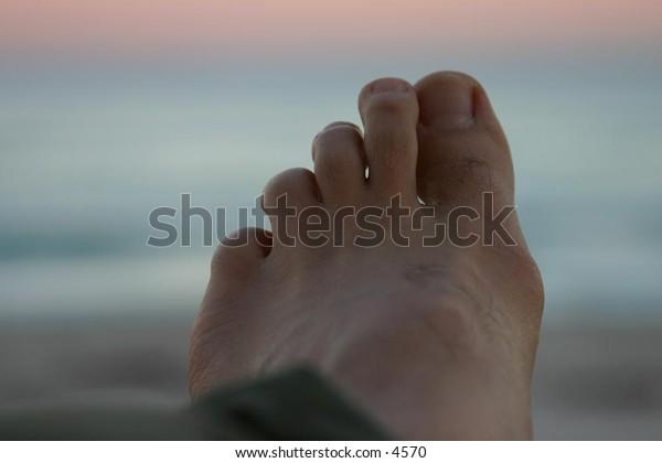 closeup of foot with beach in the background