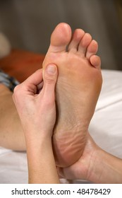 closeup of a foot of a natural mature woman having a foot reflex zone massage at the ball of the foot