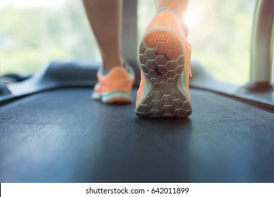 close-up footwear image, human jogging exercise on run treadmill machine cardio equipment at sport healthy club center