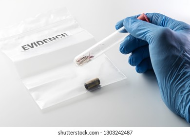 Closeup of forensic scientist's hand in blue rubber glove holding glass tube over evidence bag with 9 mm bullet case. Crime, forensic science, investigation and violence concepts.