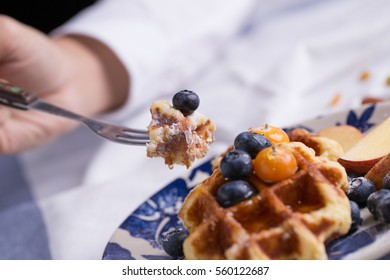 Closeup of a fork cutting a piece of blueberry waffle decorated with fresh blueberry in a nice dish.