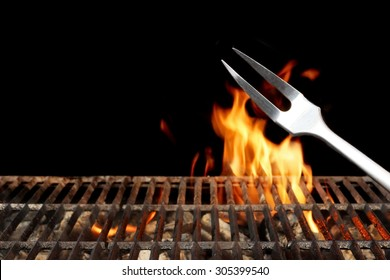 Close-up of Fork and Empty Flaming Charcoal BBQ Grill With Bright Flames On The Isolated Black Background. Weekend Barbecue Party  Or Picnic Concept.