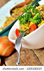 Close-up of fork and tuna risotto with vegetables, tomatoes, broccoli and parsley in the bowl, onions and pan in the background